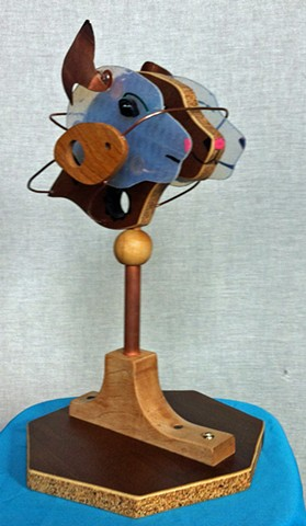 Abstract cat head in glass, wood, and more glass. Copper ears. Copper wire.