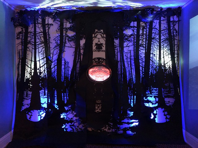 video projection, video symmetrical water cooler, cast glass mirror, paper cut forest