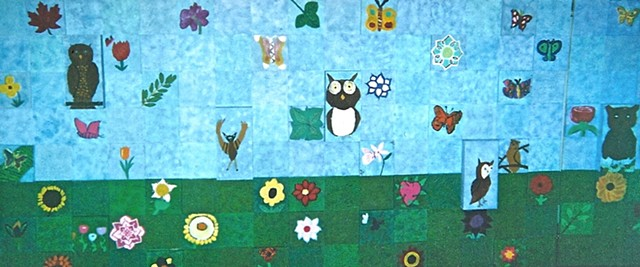 Elementary school relief sculpture mural of Owls and Garden