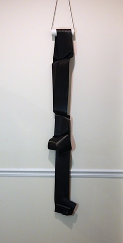 "Contemporary, minimalist, wall mounted sculpture by Robert Fields, ""Night nots/knots,"" 2019. Media: Vinyl sheet (black), metal clamps, PVC pipe, and nylon cord, 82 x 10 x 6 inches."
