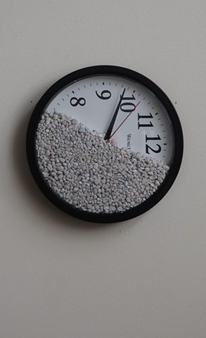 "Robert Fields, Contemporary, conceptual art. Title: ""L'me think… I remember now."" 2020. Medium: Wall clock with rock gravel (battery not included). 9-1/2"" Diameter x 1-1/2"" Deep."