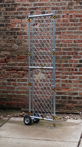 "Robert Fields, TOO MUCH! ...(Demasiados!), 2019. 69"" H x 22"" W x 12 "" D. Galvanized and painted steel pipe, wire fencing and hardware, with reflective, adhesive tape and rubber-tired wheels. A Contemporary, Performance Artwork."