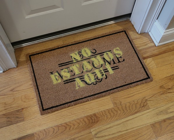 "Robert Fields, ""NOT HERE!"" ...(Enough's enough.) 2019. 18"" H x 30 "" W. Acrylic aerosol on ""WELCOME"" coco door mat. This is nuts! We are, one and all, immigrants."