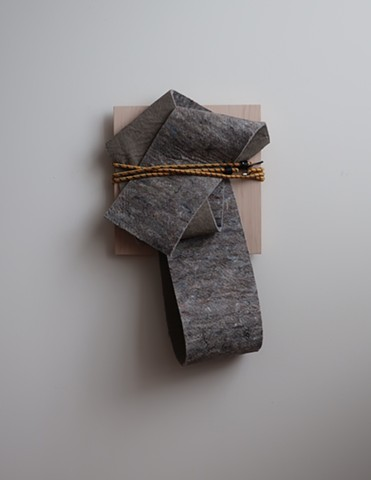 "Minimal, contemporary sculpture. Robert Fields, ""Untitled,"" 2019. Mixed fiber felt with latex foam backing, plywood panel and an elastic bungee cord. 26 H x 16 W x 7 D Inches. Contemporary artwork. Informed by stories of migration... the poems of Warsan S"