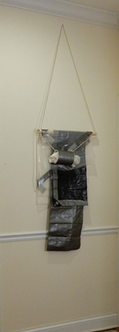 "A contemporary, wall-hung minimalist abstract sculpture with elements of formalism & materiality. A mixed media assemblage of polyethylene tarpaulin & film, adhesive tape, wood, rope and PVC pipe. ""The Doc's In."" 2018. By Robert Fields."