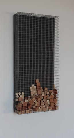 "Robert Fields, ""Nine Hundred +""  2019. Galvanized steel wire screening with copper & steel fasteners, waxed wood blocks (loose jumble), and acrylic paint on wood panel. 30-1/2 H x 14-1/2 W x 4 D Inches. Contemporary wall sculpture in a minimalist manner."