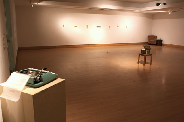 "Gallery shot of typewriter for viewer  commentary (closest) and three works:  ""Is this when the grass gets greener?"" (middle) ""Nondescript"" series (back left) ""Please, hold"" (back right)"