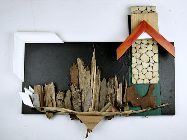 A mixed media piece by Steven Tannenbaum using nature (sticks), found wood, stones, and paint to create a skyline with buildings and other various shapes