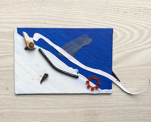 A small abstract fish sculpture using found objects, acrylic paint, and collage