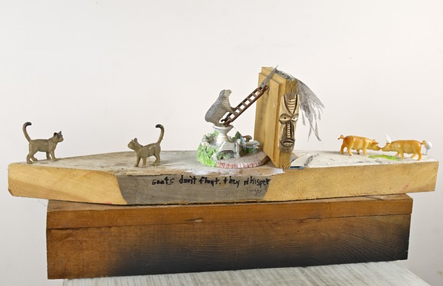 Linger is a Modern Assemblage Art piece using found objects and barn animals along with a voodoo mask, written word, and fencing to create a barnyard scene with cats, goats, sheep, pigs, and horns.