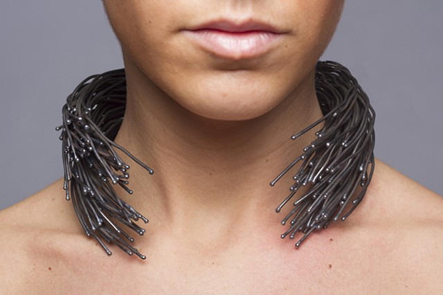 A sculptural one-of-a-kind forged wire neckpiece that is composed of welded steel