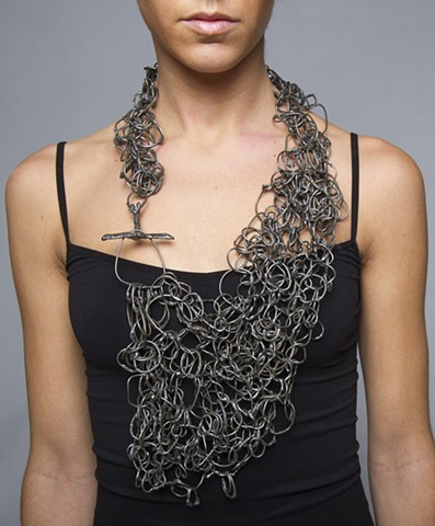 a one-of-a-kind chainmail neckpiece composed of hand formed steel wire chain links that have been welded together