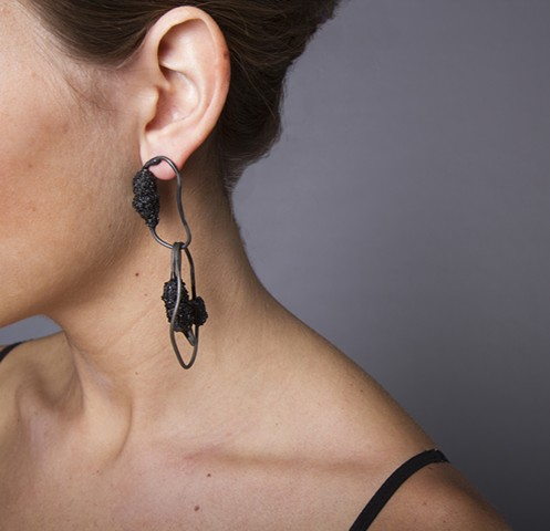 a one-of-a-kind pair of earrings that are composed of welded steel wire chain links and a handmade bead composed of broken black vine charcoal, powdered graphite, lacquer and plastic dip.