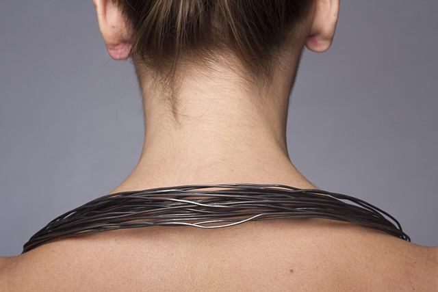 a one-of-a-kind steel wire neckpiece that is composed of welded raw steel wire, black crepe paper, string, lacquer and plastic dip