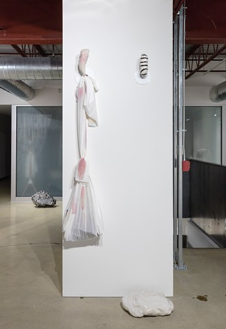 Installation view showing 'Really It's A Lot Bigger, A Lot Heavier, And A Lot Darker #18' and 'Bindle bundle v. 01 (with purple Doritos—Spicy Sweet Chili—poopy diaper/baby carried by stork/Liz Magor hoard) and some visual extrapolation—brown stripes, porc