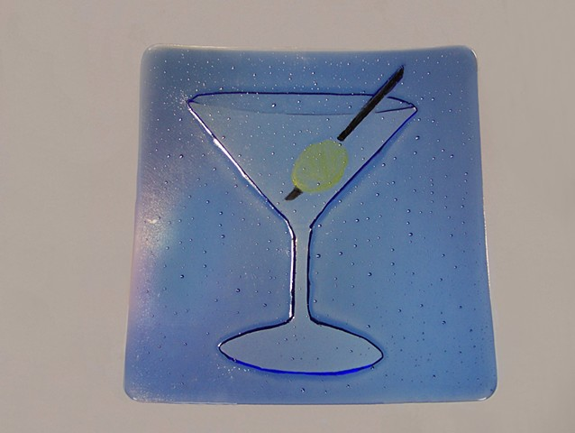 A kiln carved martini in blue glass complete with green olive.