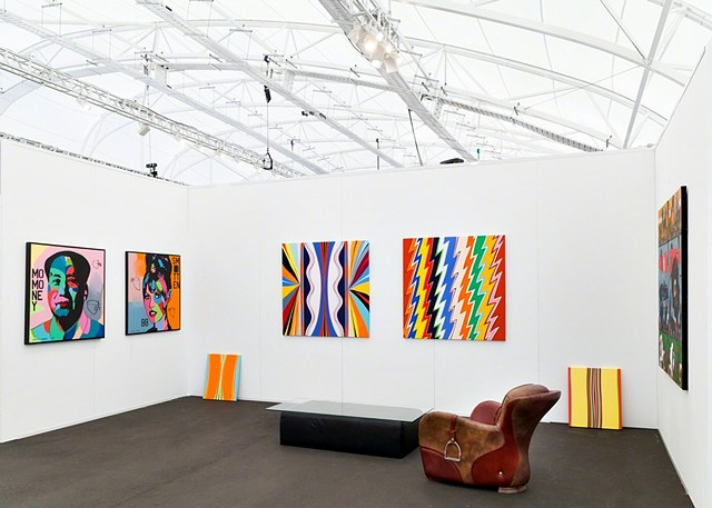"2018 Auckland Art Fair, Auckland, New Zealand represented by 12 Gallery.  Center Wall ( ""Maybelle"" and ""Pollenator"").  Both works 48 x 48"", acrylic on canvas.  Color Bombs. The work of Johnny Romeo is on the left."