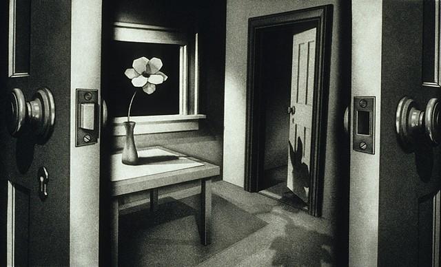 Black and white scene, doorway, flower on table, shadow of a rabbit on door