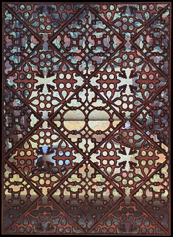 Islamic screen in front of 2 cups on table, looking to horizon through holes