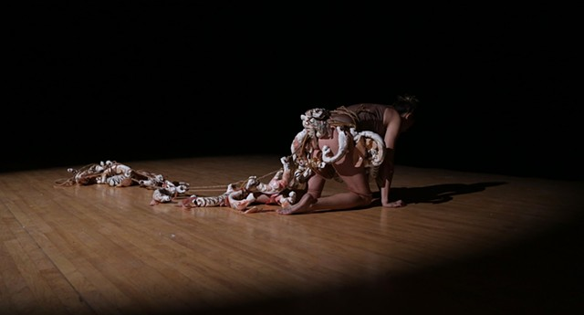video of a performance where I am wrapping myself with a sculpture made out ceramics, twine, latex tubing, and paper. Collecting these objects that resemble fish or bones onto myself that eventually become almost too heavy to carry.