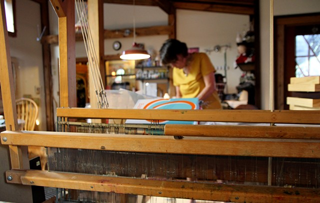 The artist works on a recent piece framed by her loom.