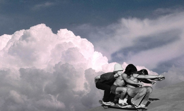 Three guys riding a long skateboard appearing to come from a cloud on to Earth