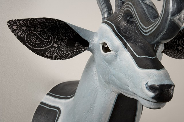 low rider sculpture of a deer with snake on its head and painted with iridescent white and payns gray pin stripping of blue black oil paint