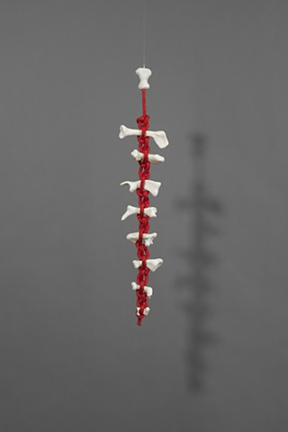 abstract hanging sculpture by Laura Evans suggesting a spine. Figurative