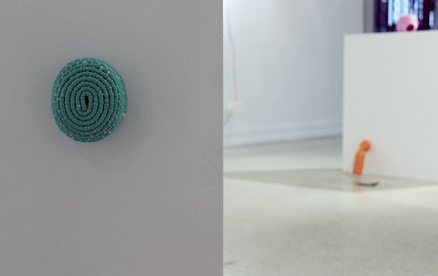 contemporary coiled basket sculpture made of mint plastic lacing with two sculptures in tangerine and pink in the background by Jose Santiago Perez