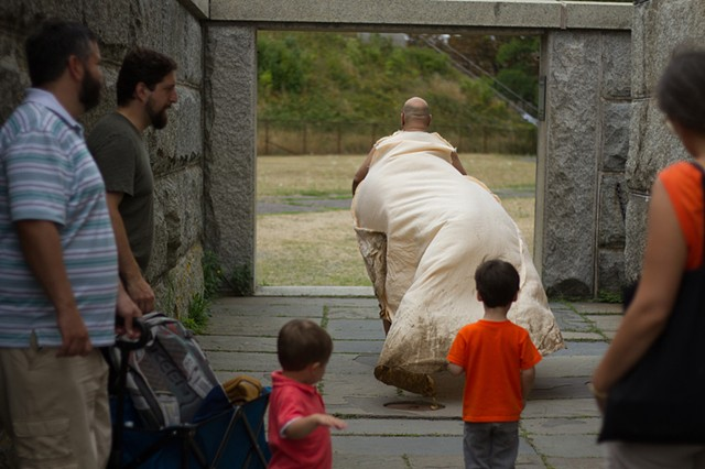 walking performance by Jose Santiago Perez with family of onlookers at Georges Island Boston