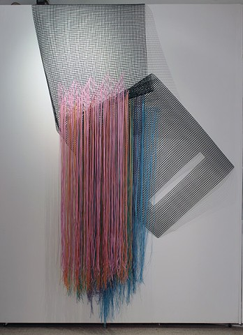 Installation view of wall hanging in multicolored plastic lacing by Jose Santiago Perez
