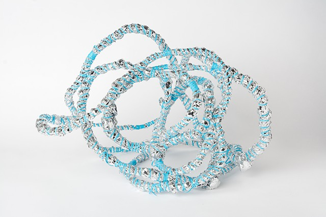 abstract basket made of baby blue plastic lacing and emergency blankets by Jose Santiago Perez