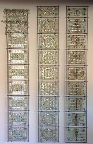 "fused glass, mica, wire, and bead panels arranged in three 54""x8"" steel grids"