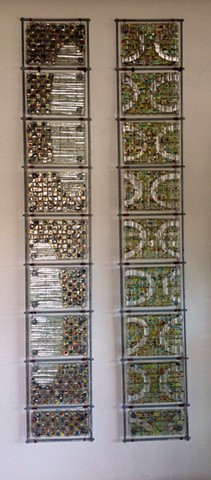 "fused glass, mica, wire, and bead panels arranged in 8""x54"" grids"