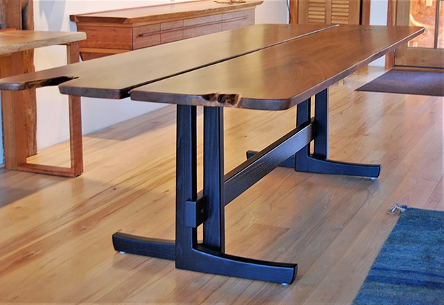 Opposing Leg Trestle Table, book-matched walnut slabs with crotch flame figure on ebonized ash trestle base.  38 in. x 100 in. x 30 in. high.  The table top comes apart at the seam and the base packs flat for shipping.