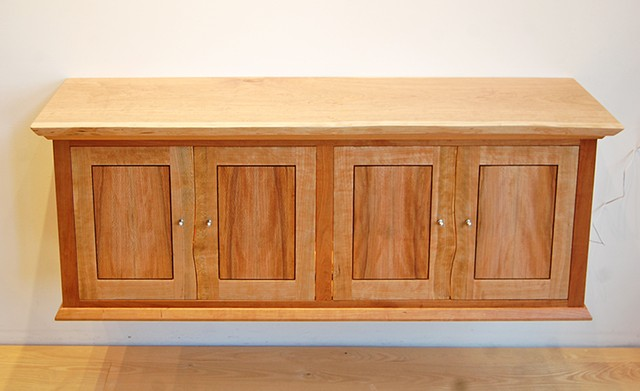 Cherry wall hung bar cabinet with live edge doors, quarter-sawn sycamore panels, motion activated interior lighting. 14 x 50 x 20 h