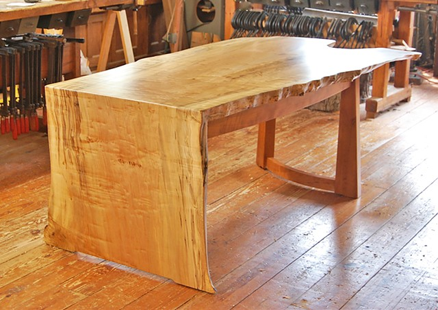 Arnold desk, featuring a one-piece waterfall top made from highly figured maple, locally sourced.  It sits on a cherry base with a single row of drawers.  Approx. 38 x 84 x 30 high.