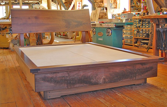 Goldyne queen-size platform storage bed.  Walnut live edge headboard with matching drawer fronts and book-matched crotch-grain footboard.  Eight drawers total.