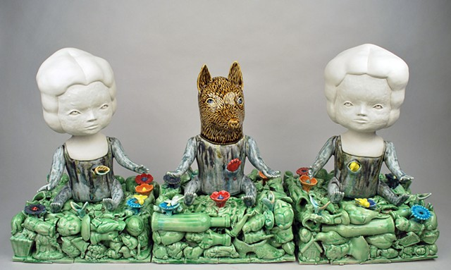 Three coiled porcelain fgures sitting on bases made from slip cast porcelain objects.  Two doll figures and one wolf with carved head