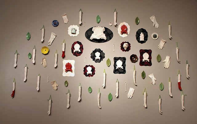Wall installation with cast porcelain found objects and clocks, porcelain arms, flocking, ladies white gloves, doll figures, flowers and leaves