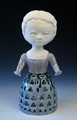 Porcelain doll figure with pierced, patterned skirt.  The skirt contains small cast porcelain knick knack objects.  Coil built.