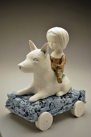 Coil built doll figure seated on a carved porcelain dog and riding on a wheeled cart made from cast porcelain objects.