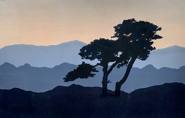 Silhouetted tree at dusk with three mountain ranges