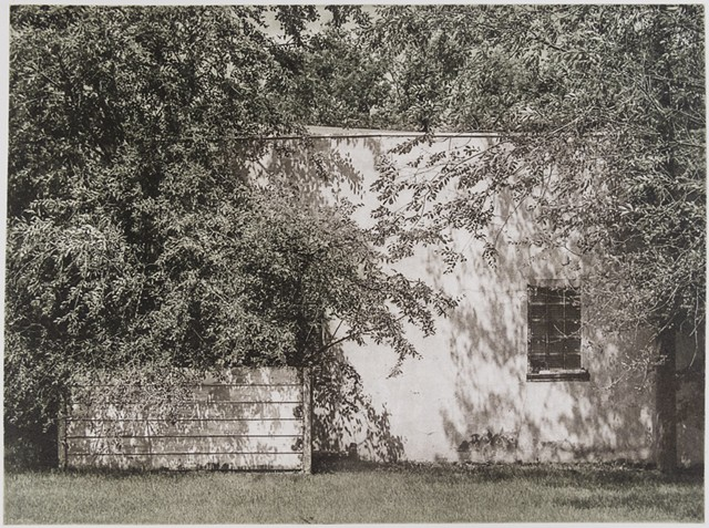 In a small town in North Dakota, a stucco shed wall is dappled by shade in this polymer photogravure print by John Pearson.