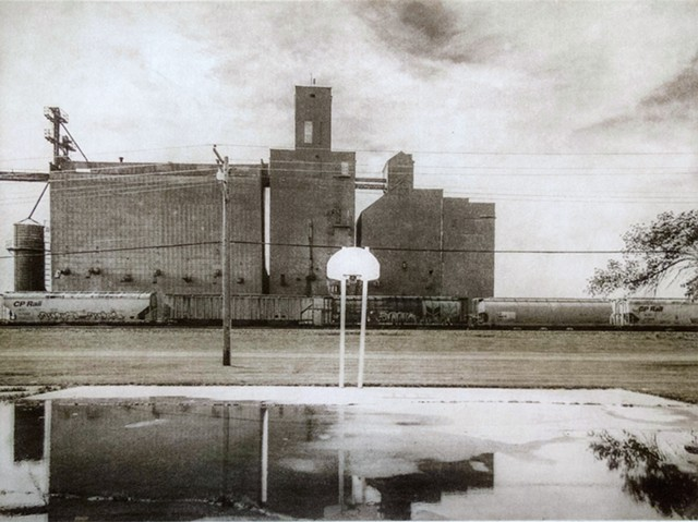 Basketball court near a railroad siding and elevator in Oslo, Minnesota. One-plate polymer photogravure print on pescia paper by John Pearson.