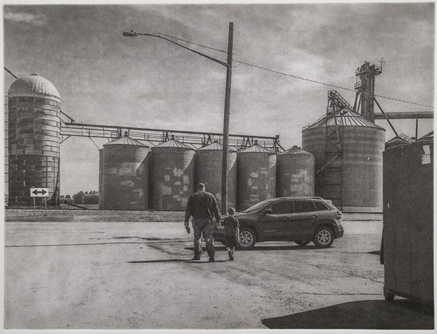 Polymer photogravure intaglio print of a man and young boy walking towards grain elevators in Larimore, North Dakota.