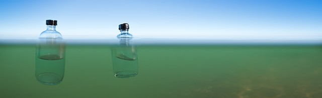 Bottles of water from the Pacific Ocean and Kiwassa Lake floating in Lake Michigan