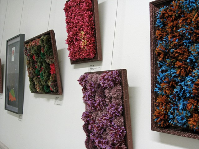 sculpture installation of brown glittered picture frames and multicolored yarn pom poms old redmond school house by Holly Campbell