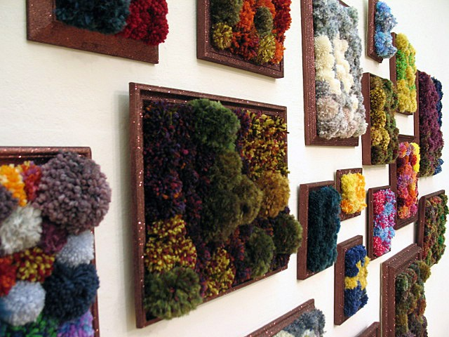 sculpture installation of brown glittered picture frames and multicolored yarn pom poms by Holly Campbell