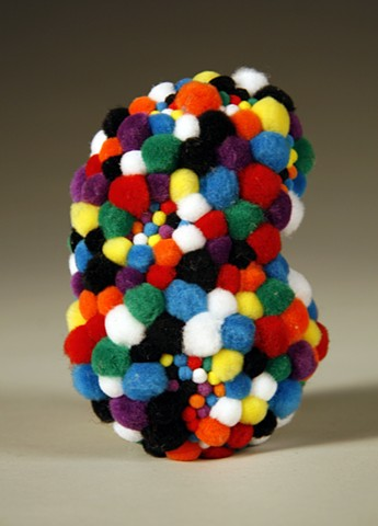 sculpture found rock covered in rainbow black white pom poms kidney shaped by Holly Campbell
